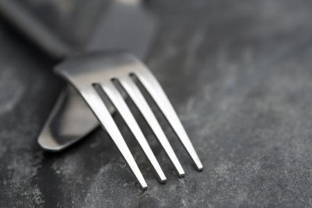 Macro beeld van de moderne mes en vork op een rustieke lei achtergrond Stockfoto