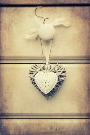 Macro retro cross processed effect image of tin and willow hearts on wooden background photo