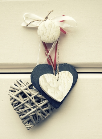 Macro retro cross processed effect image of willow, slate and wooden hearts on wooden background photo
