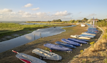 sunlgiht: Boats moored at low tide in marina on Summer evening Stock Photo