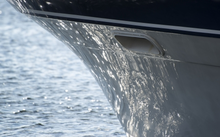 Detail image of sea reflecting on hull of yacht sailboat photo