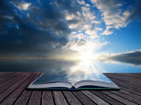 Creatief concept pagina's van het boek Prachtige landschap bij zonsondergang weerspiegeld in de oceaan