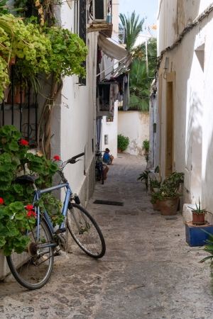 Mediterranean alley way between old houses and buildings with bike and local residents photo