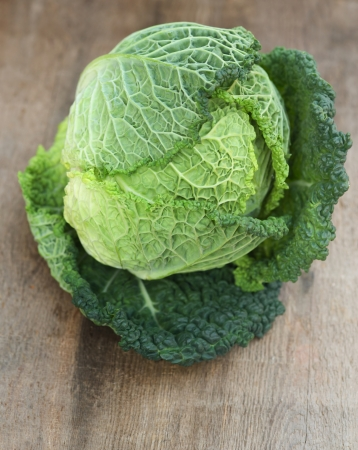 Fresh Savoy Cabbage on wooden background photo