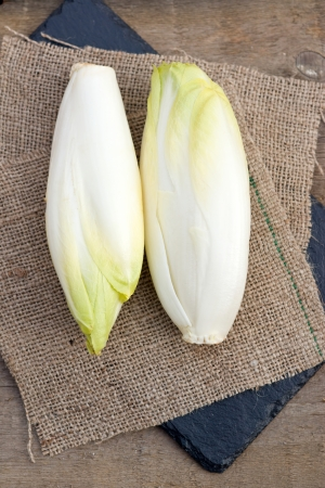 Fresh chicory heads on rustic slate and wood background