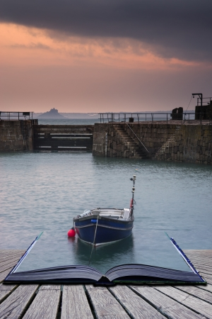 Creative concept pages of book A traditional Cornish fishing village before sunrise in Cornwall England photo