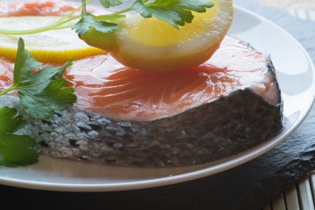 Fresh raw salmon cutlet with lemons and parsley garnish photo