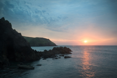 Sunset landscape seascape of rocky coastline at Hope Cove in England photo