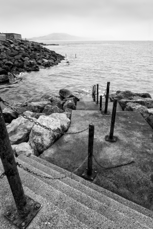 rungs: Black and white image of old steps leading down into sea