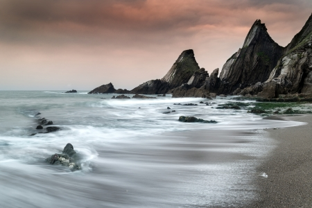 Rugged long exposure landscape seascape of rocky coastline photo
