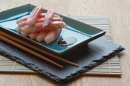Raw fresh sushi carbsticks on plate with chopsticks Stock Photo - 23957754