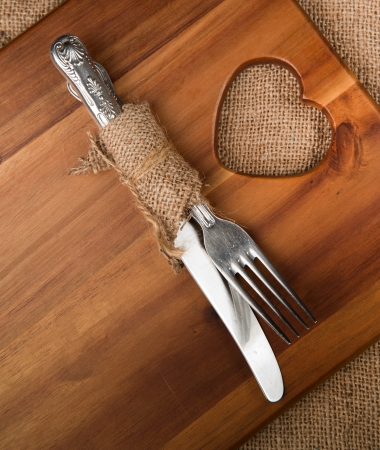 Vintage knife and fork in hessian on acacia wood board photo