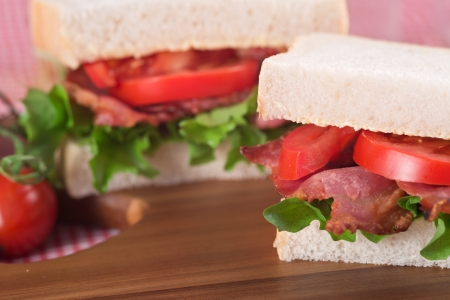 Rustic kitchen setting for fresh BLT on white sandwich photo