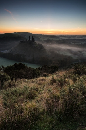 Vibrant sunrise over medieval castle ruins with fog in rural landscape photo