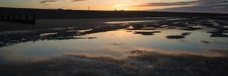 Beautiful sunrise panorama landscape reflected in pools on beach photo