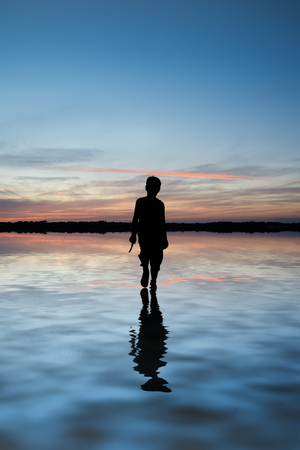 niños caminando: Imagen conceptual de joven caminando sobre el agua en la puesta del sol del paisaje Foto de archivo