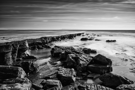 Stunning black and white seascape coastline and rocky shore at sunset Stock Photo