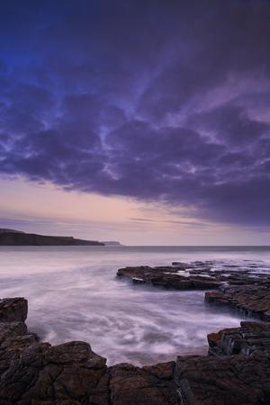 Stunning toned landscape seascape coastline and rocky shore at sunset