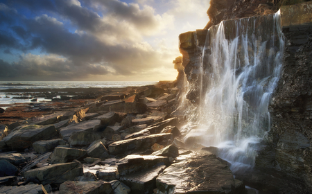 Beautiful landscape waterfall flowing into rocks on beach at\ sunset