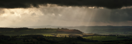 pano: Panorama landscape dramatic sky with sun beams over countryside during Autumn