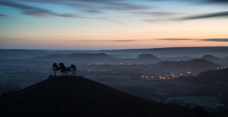 valley below: Beautiful sunrise dawn landscape of countryside overlooking brightly lit town in valley below Stock Photo