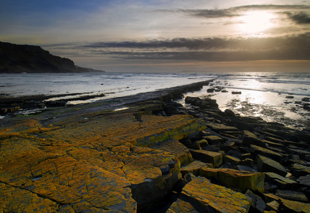 Stunning landscape seascape coastline and rocky shore at sunset