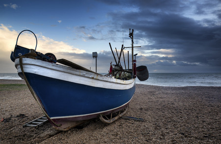 industry moody: Fishing boat on shingle beach landscape with stormy sky