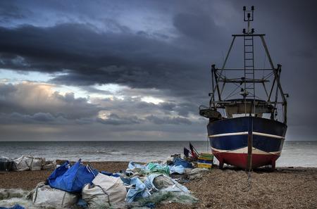 beach shingle: Barca da pesca sulla spiaggia di ciottoli paesaggio con cielo tempestoso Archivio Fotografico