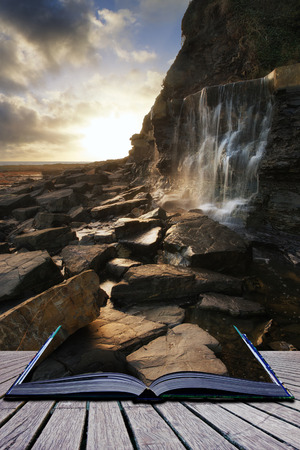 Book concept Beautiful landscape waterfall flowing into rocks on beach at sunset