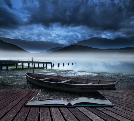 storytelling: Book concept Stormy sky landscape over misty mountain lake with old boat on lake shore