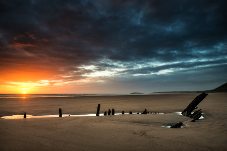 Dramatic sunset landscape over shipwreck on Rhosilli Bay beach photo