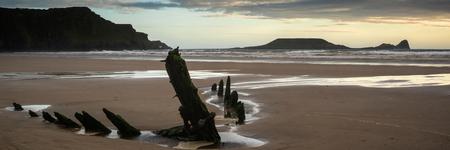 sunlgiht: Landscape panorama shipwreck on Rhosilli Bay beach in Wales at sunset Stock Photo