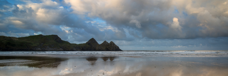 spring tide: Sunrise landscape panorama Three Cliffs Bay in Wales