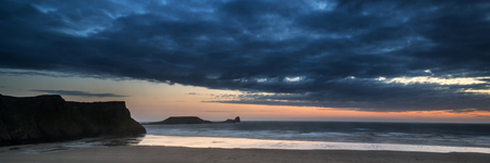 Landscape panorama Rhosilli Bay beach at sunset with dramatic sky