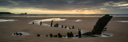 Landscape panorama shipwreck on Rhosilli Bay beach in Wales at sunset Stock Photo