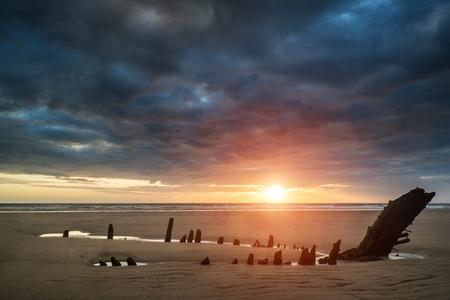 Dramatic sunset landscape over shipwreck on Rhosilli Bay beach photo