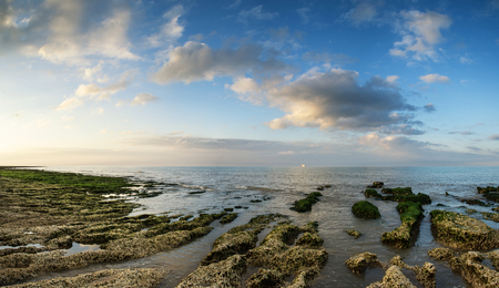 Panorama landscape looking out to sea with rocky coastline and beautful sunset sky photo