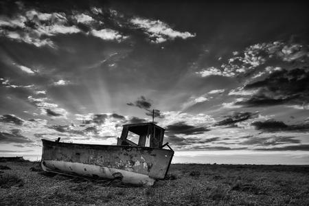 beach shingle: Barca da pesca abbandonata sulla spiaggia di ciottoli nero e bianco paesaggio al tramonto
