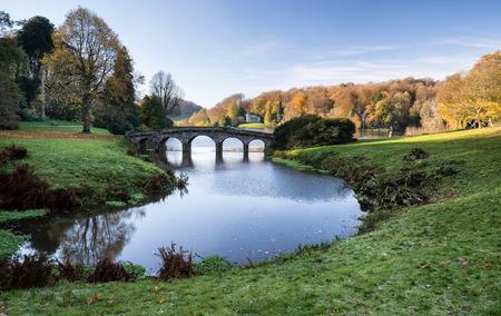 stourhead: Bridge over main lake in Stourhead Gardens during Autumn. Stock Photo