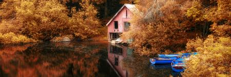 Panorama landscape stunning Autumn scene boat lake and boathouse photo