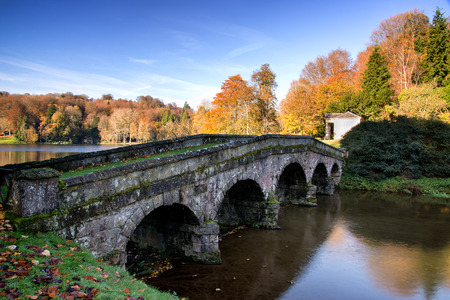 stourhead: Bridge over main lake in Stourhead Gardens during Autumn. Stock Photo
