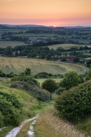 sunlgiht: Summer sunset landscape overlooking English countryside