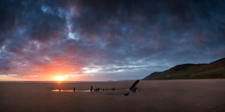 Landscape image of shipwreck on beach at sunset in Summer photo
