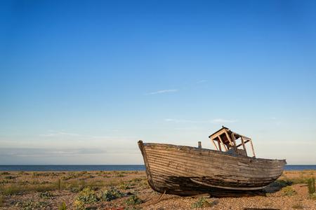 beach shingle: Barca da pesca abbandonata sulla ghiaia paesaggio spiaggia al tramonto Archivio Fotografico