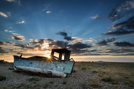 Abandoned fishing boat on shingle beach landscape at sunset photo