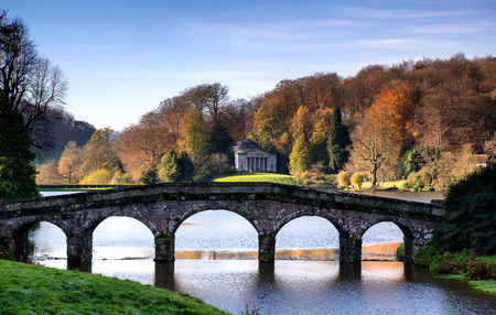 stourhead: Bridge over main lake in Stourhead Gardens during Autumn. Editorial