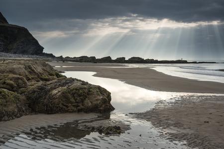 stunning: Stunning sun beams bursting from sky over empty yellow sand beach landscape