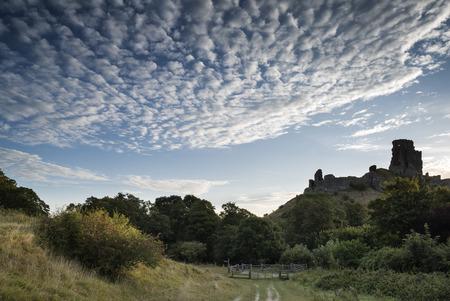 Stunning sunrise landscape over ruins of medieval castle photo