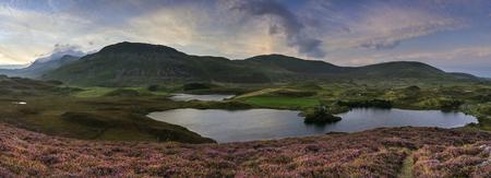 Stunning sunrise panorama landscape of heather with mountain lake and mountain range photo