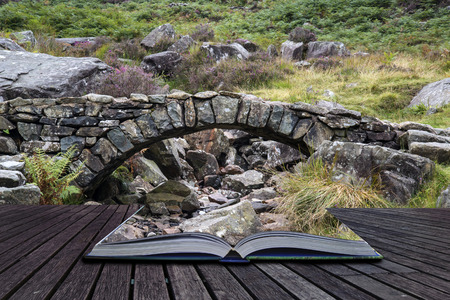old packhorse bridge: Old ancient packhorse bridge over mountain stream conceptual book image Stock Photo